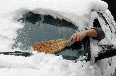 фото: мужик очищает машину от снега