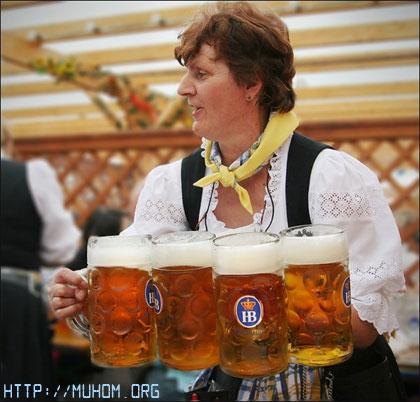 Женщина несёт много кружек пива
